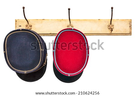 Two vintage conductor hats hanging on a hat-rack isolated on a white background - stock photo