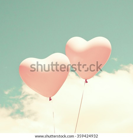 Two vintage pink heart-shaped balloons over a blue sky - stock photo