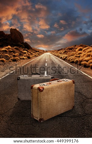 Two vintage suitcases in the middle of a grungy asphalt road leading through desert landscape - stock photo