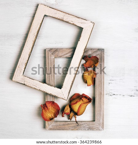 Two vintage wooden photo frames with dried roses on shabby painted wood background.  - stock photo