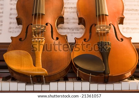 Two violins resting on top of piano keys - stock photo