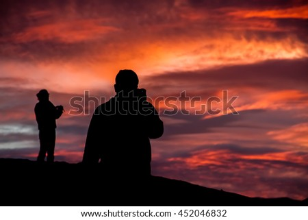 Two visitors capturing a massive sunset at Zabriskie Point, Death Valley National Park, CA, November 29, 2013