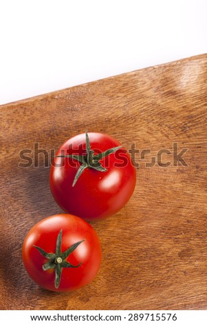 Two vivid red fresh tomato on the wood dish(tray, bowl) isolated white reflected at the studio.