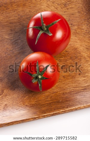 Two vivid red fresh tomato on the wood dish(tray, bowl) isolated white reflected at the studio. - stock photo