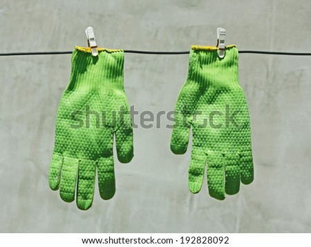 Two vividly green gloves hanging on a wire on a background of gray wall in bright sunlight