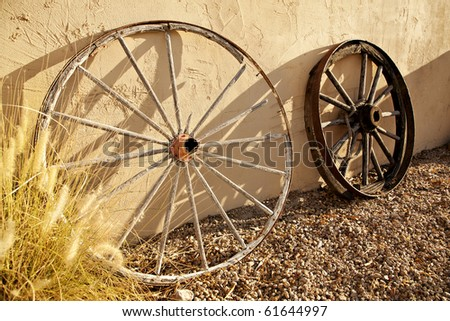 Two wagon wheels of the old American West, leaning against a stucco wall in the late afternoon sun.