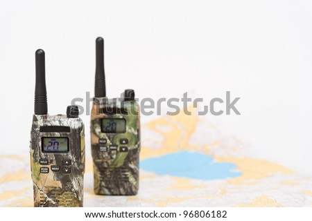 Two walkie-talkies and map on the background. - stock photo