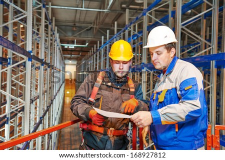 two warehouse worker in front of rack stack in storehouse - stock photo