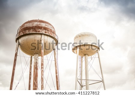 Two water towers and cloudy sky, United States - stock photo