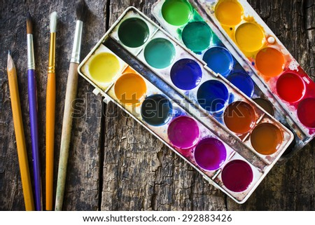 Two watercolor paint and pencil, different fan brush to paint on an old wooden table - stock photo