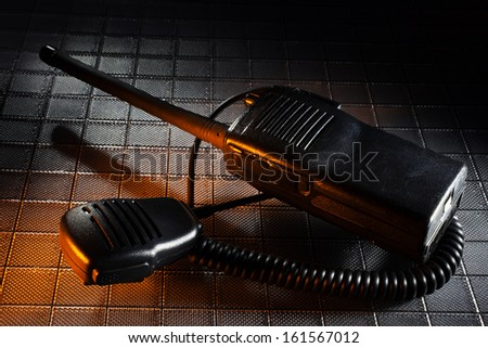 Two way radio and microphone on a textured background with orange - stock photo