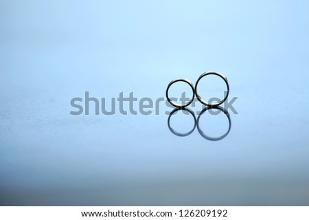 two wedding golden on glass surface - stock photo