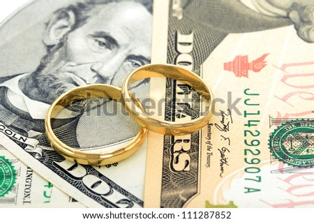 Two wedding rings and money as symbol f���¼r an expensive alliance - stock photo
