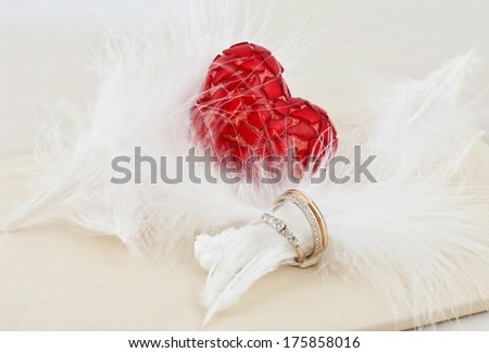 two wedding rings and one heart - stock photo