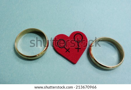 Two wedding rings and red heart with female gender symbols - gay marriage concept                                - stock photo