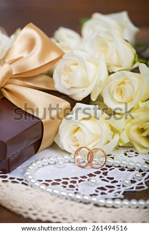two wedding rings and white roses