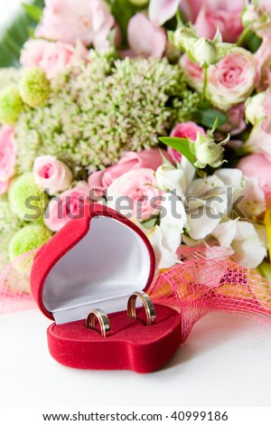 Two wedding rings in a box infront of flowers - stock photo
