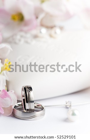 two wedding rings, necklace and ear rings with flowers and a heart - stock photo
