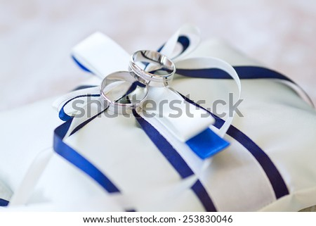 two wedding rings on pillow decorated with white and blue ribbon bows - stock photo