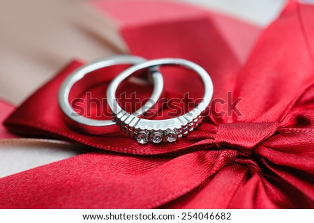 two wedding rings on red background. - stock photo