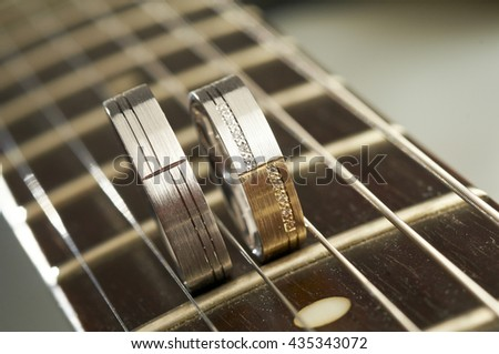 Two wedding rings standing on guitar fretboard