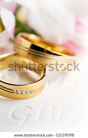 two wedding rings with flowers in the background - stock photo