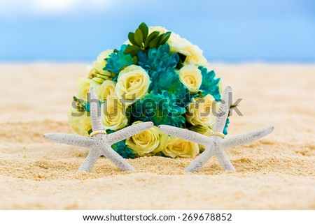 Two wedding rings with two starfish and wedding bouquet on a sandy tropical beach. Wedding and honeymoon in the tropics. - stock photo