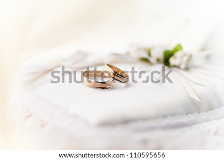 Two wedding rings with white bow in the background. - stock photo