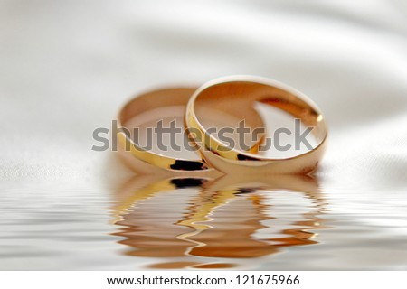 Two wedding rings with white flower in the background, wedding photo - stock photo