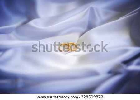 Two weddings rings on background of fabric - stock photo