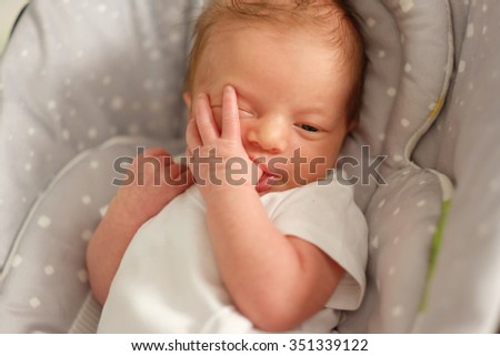 Two weeks old newborn baby in infant seat