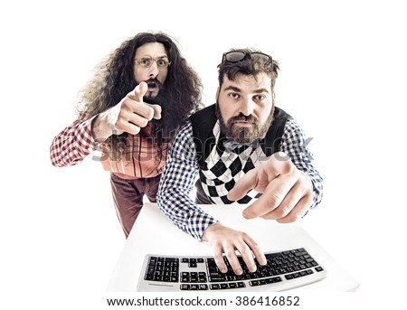 Two weird computer geeks having fun on computer - stock photo