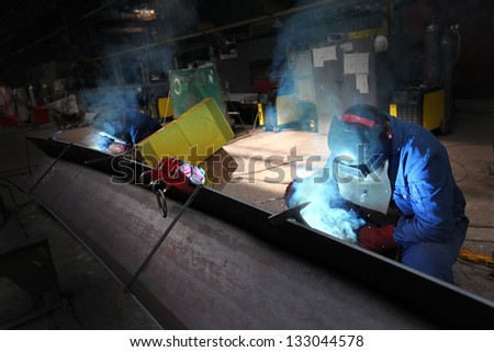 two welders workers in the factory