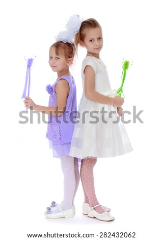 two well-dressed girl holding a magic wand- isolated on white background - stock photo