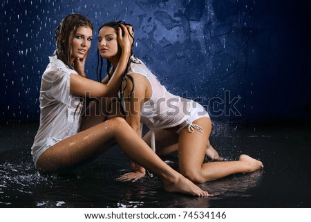 Two wet semiundressed sexy girls on a dark blue background in water splashes - stock photo