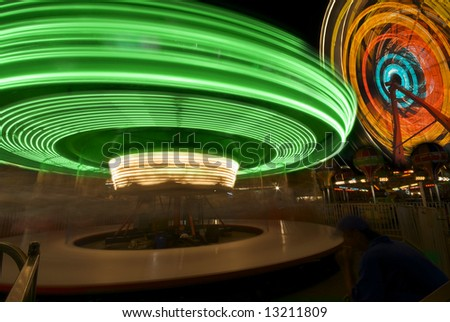 Two whirling carnival rides create magical and colorful rings of light in the night