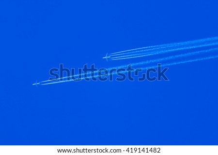 two White airliners pulling white contrails in dark blue cloudy sky - stock photo