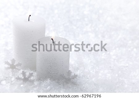 Two white candles on white snow background - stock photo