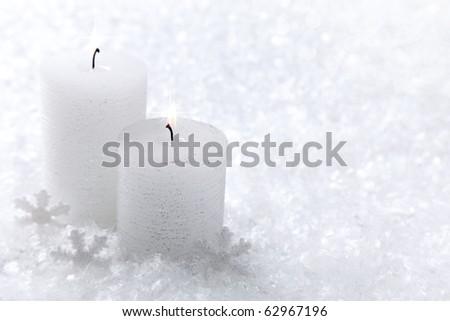 Two white candles on white snow background - stock photo