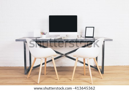 Two white chairs next to designer table with blank computer screen and other items on wooden floor and brick background. Mock up - stock photo