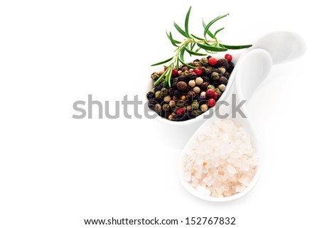 Two white china spoons filled with Himalayan rock salt crystals and black peppercorns with a sprig of fresh rosemary over white with copyspace - stock photo