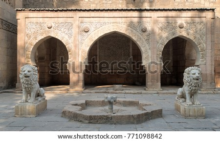 Two white marble lions statues and decorative fountain in front of three adjacent decorated stone arches at the garden of Manial Palace of Prince Mohammed Ali located in Manial district, Cairo, Egypt