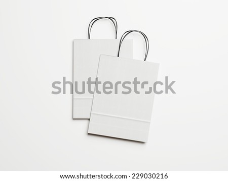 Two white paper bags with black handles - stock photo