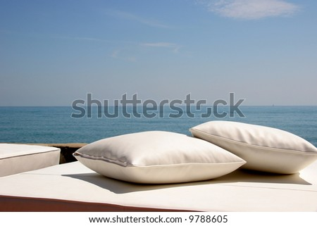 Two white pillows on a sunlounger by the sea - stock photo