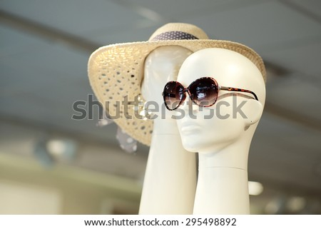 Two white plastic mannequin heads in sunglasses and summer hat indoor on shop background, horizontal picture - stock photo