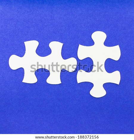 Two white puzzle with blue background - stock photo