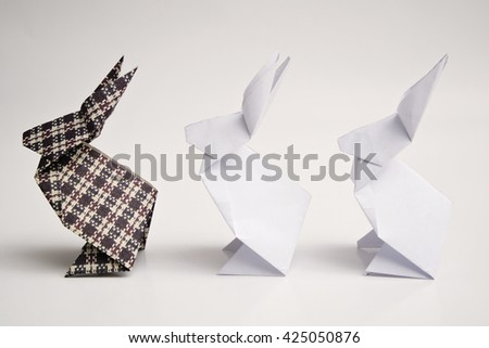 Two white rabbits origami and a black rabbit origami - stock photo
