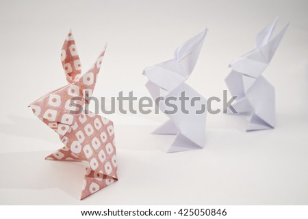 Two white rabbits origami and a pink rabbit origami - stock photo