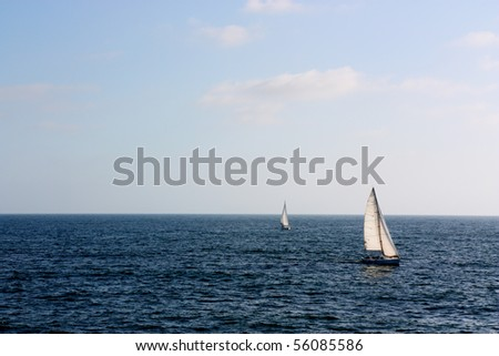 Two white sail yachts in wide open blue ocean waters