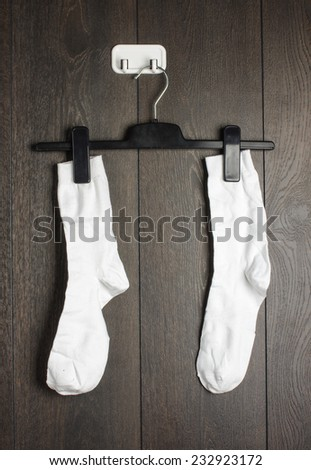 Two white socks hanged on the wall - stock photo